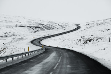 Uphill road landscape in winter at Iceland. Asphalt road with sideways full of snow