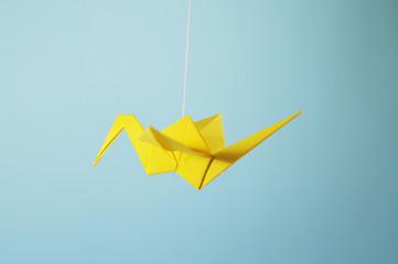 yellow origami crane flying