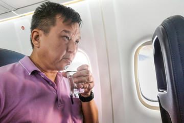Person drinking water in airplane long haul flight to hydrate