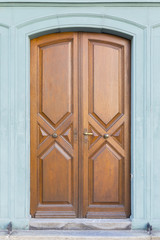 A vintage style carved wooden door with geometric patterns and light green painted wall