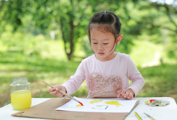 Child painting, little girl having fun to paint on paper in the green garden.