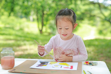 Asian child girl painting with paintbrush on arts paper on the table in the green garden.