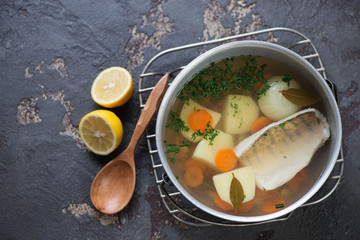 Above view of fish soup with sudak in a kettle on a brown stone background