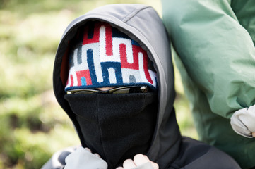 masket person with sunglasses and hood