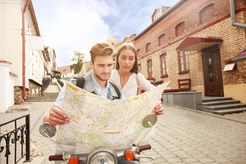 Young Couple with scooter looking at map.