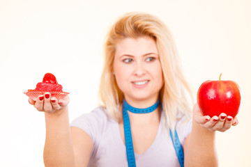 Woman choosing between apple and sweet cupcake