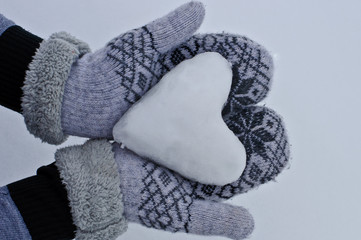women's hands in cozy warm mittens keep the heart out of the snow against the background of snow
