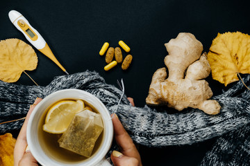 Closeup Women's hands with Tea, lemon, thermometer, ginger, scarf, tablets and dry leaves on a black background. Cold illness concept, top view, flat lay.