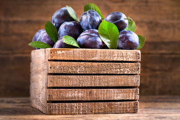 fresh plums with leaves in a wooden box