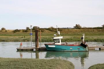 Kleines Fischerboot an einem Holzsteg