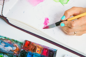 A close-up as an artist with blue nails draws pink flowers with a wooden brush and watercolors in the aluoma for drawing, on the table lie a palette for drawing