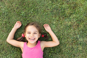 Happy Smiling Little Girl Laying On Grass In Park