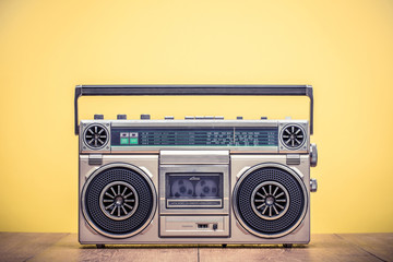Retro outdated portable stereo boombox radio cassette recorder from 80s front yellow background. Vintage instagram old style filtered photo