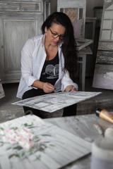 pittrice seduta lavora ad un suo quadro