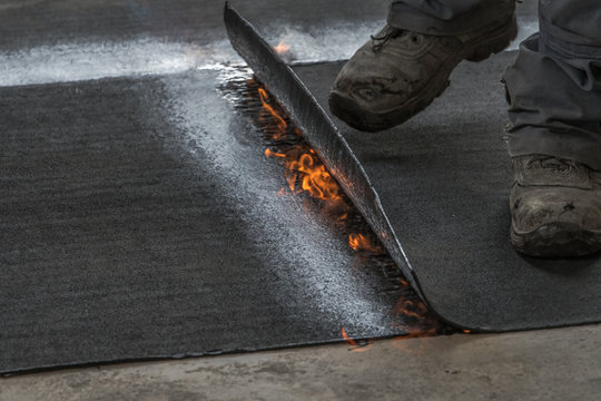 Professional installation of the waterproofing on the concrete foundation. Installation with rolls of bituminous sealing membrane by heating and melting of bitumen rolls by torch to flame while sealin