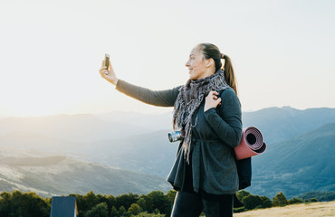 Woman traveler takes pictures on the phone mountains at dawn