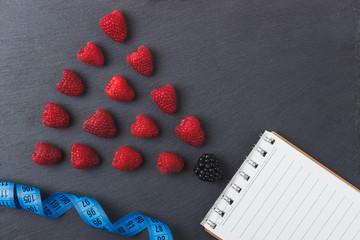 Red raspberries, tape measure, notebook on the black slate stone background