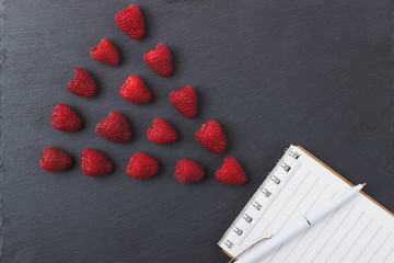 Red raspberries, tape measure, notebook and a pen on the black slate stone background