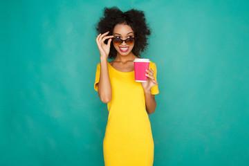 Happy mulatto girl drinking coffe at studio background