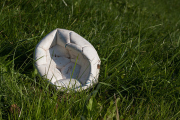 deflated soccer ball on green grass/deflated soccer ball/sports allocated objects