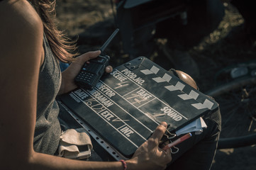 Woman holding clapperboard against her face