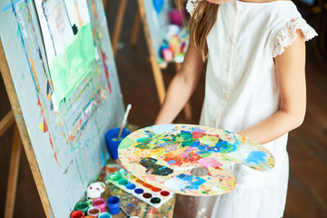 Mid section portrait of unrecognizable girl painting on easel during art class holding color palette in hand