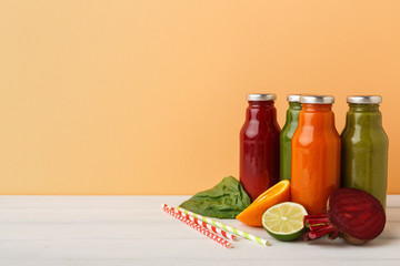 Assortment of detox smoothies in glass bottles on wall background.