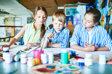 Group of three children, two girls and one boy,  painting together in art class sitting at big table with art supplies, pencils and paints
