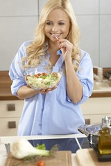 Pretty woman tasting salad