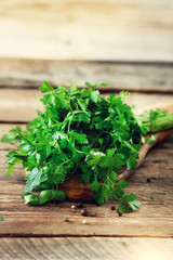 Bunch of fresh organic parsley on wooden background with copyspace, rustic and vintage style, selective focus, free space for your text