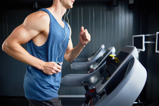 Unrecognizable muscular man in headphones enjoying favorite song while running on treadmill during intensive workout at modern gym