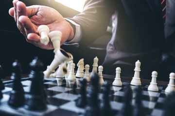 Close up of hands confident businessman colleagues playing chess game to development analysis new strategy plan, leader and teamwork concept for success.