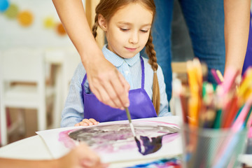 Portrait of unrecognizable teacher helping pretty little girl finish her painting in art and craft class of pre-school