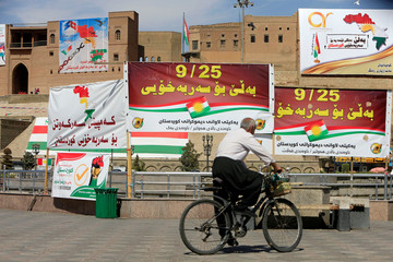 An old man rides a bike near banners supporting the referendum for independence of Kurdistan in Erbil