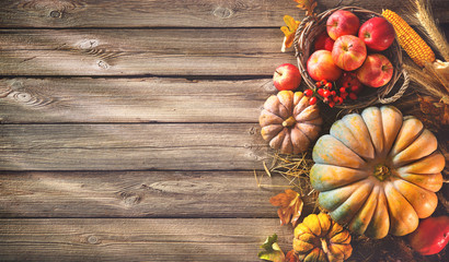 Thanksgiving background with pumpkins and falling leaves on rustic wooden table