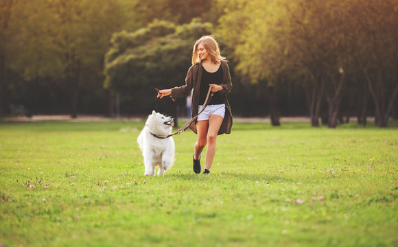 Pretty girl playing and running with samoyed dog at the park