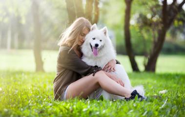 Pretty girl hugging her dog at the park, samoyed