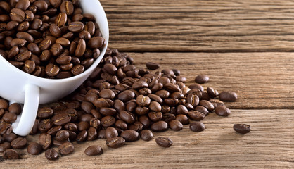 Coffee beans with white cup on wooden table.