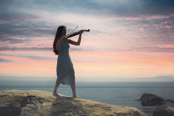woman playing violin at sunset at the sea