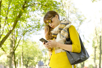 Cute woman is reading pleasant text message on mobile phone while taking a walk in the park  in warm fall day