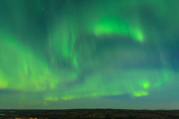 The Aurora in the sky above the hills at night .