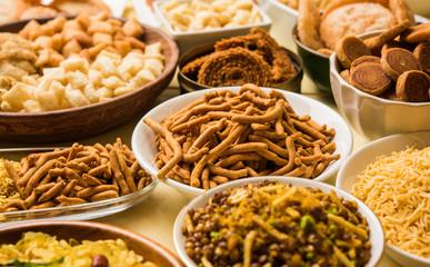 stock photo of  Diwali food or Diwali snacks or Diwali sweets like anarsa, bakarvadi, chakli, sev, bhujiya, shankar pale and chivda or chiwada, karanji, favourite indian diwali recipe