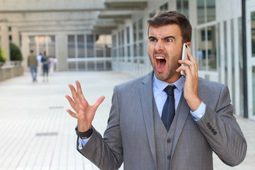 Desperate young brunette businessman get bad news heavy problems, faces challenges snort while talking on the mobile phone