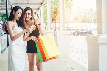Happy women using phone Enjoying Spending shopping bags in Fashion shopping street