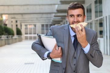Businessman walking, eating and talking on the phone at the same time