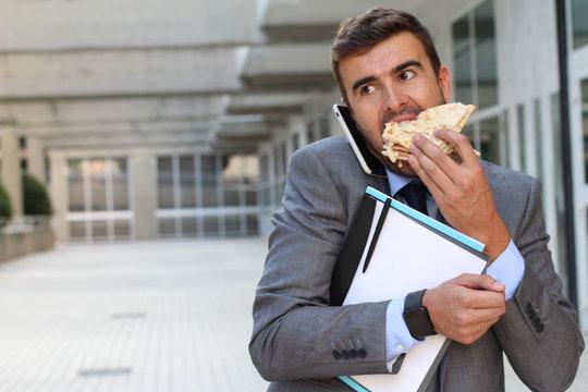 Businessman eating a sandwich on the go
