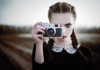 Lovely sad young girl photographing on vintage film camera. Closeup outdoor portrait