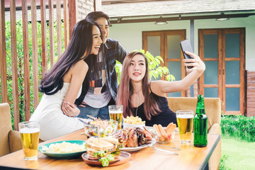 Group of friends are taking selfie and eating food are happy enjoying in home