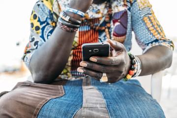 Crop black man using phone