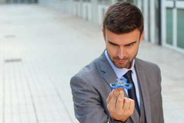 Cute businessman playing with a hand spinner